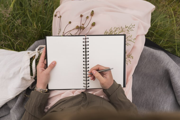 Image: Woman Sitting Writing Down Something in Her Notebook