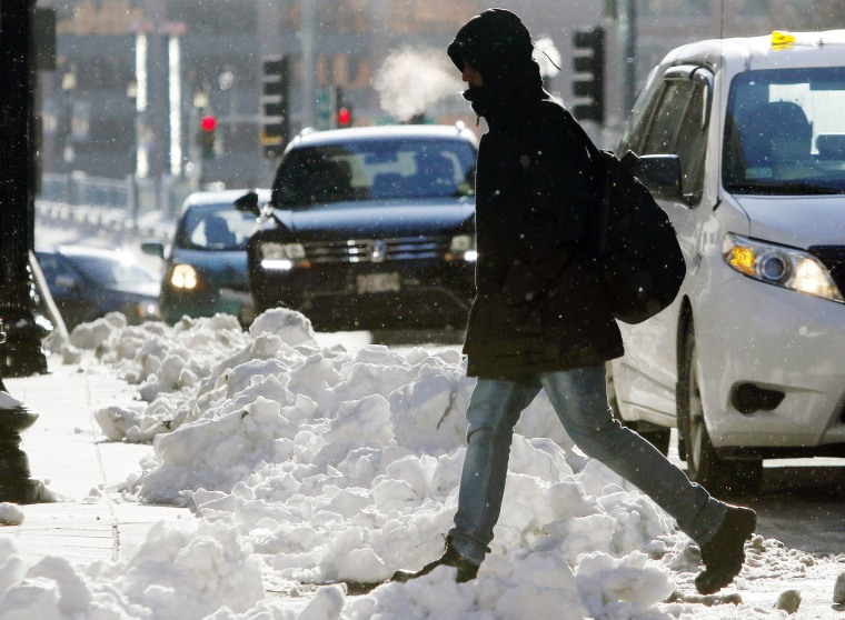 Image: A pedestrian crosses the street as the temperature hovers in the single-digits