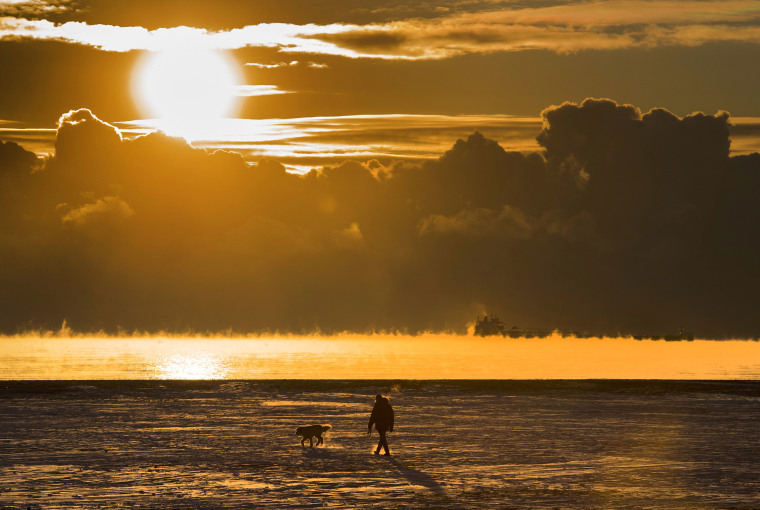 Image: A man walks his dog across the snow covered beach