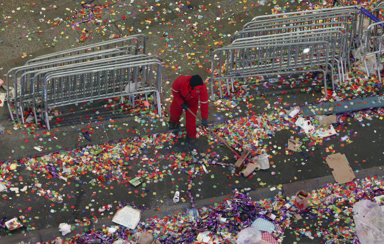 Image: A member of the cleanup crew sweeps confetti in New York's Times Square