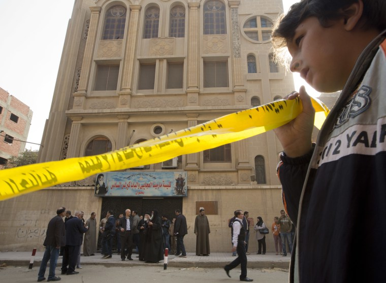 A boy holds yellow tape surrounding the site in front of Mar Mina church, in Helwan, Cairo on Dec. 29, 2017.