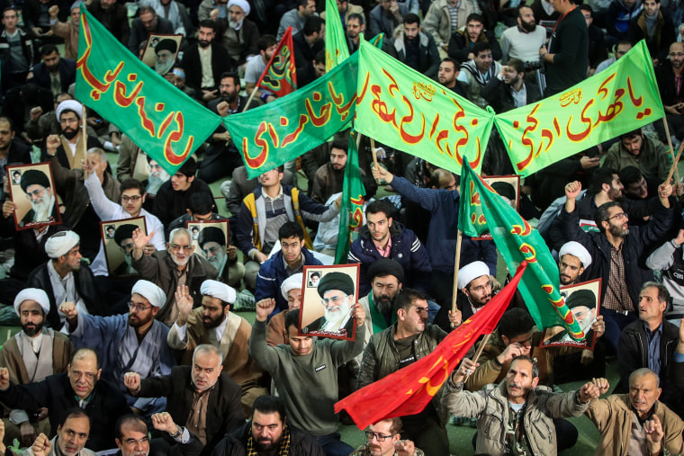 Image: Iranians chant slogans as they march in support of the government near the Imam Khomeini grand mosque