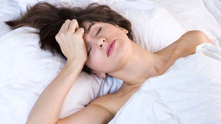 Woman restless in bed, hungover