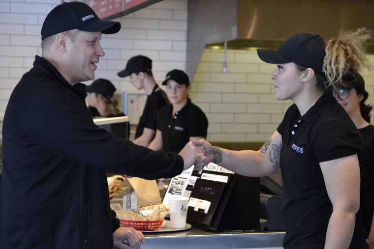 Bruce Wayne shakes hands with a Chipotle employee after eating a record-breaking meal.