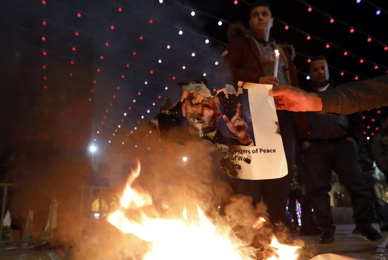 Image: Palestinians burn a picture of U.S. Vice President Mike Pence during a protest against U.S. President Donald J.Trump's decision to announce Jerusalem as the capital of Israel and the visit of Pence in the West Bank city of Bethlehem, Dec. 17, 2017.