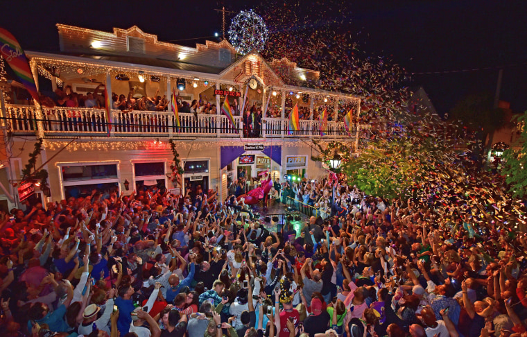 Image: Revelers celebrate as female impersonator Gary Marion is lowered during the Red Shoe Drop, at Duval Street in Key West, Florida