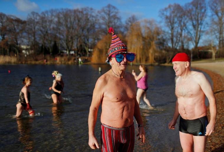 Image: Members of the Berliner Seehunde ice swimmers club take a dip in lake Orankesee during their traditional New Year swimming event in Berlin