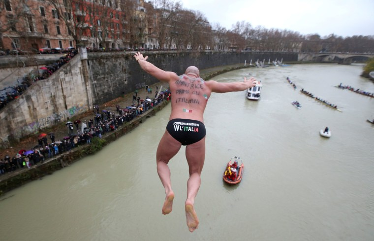 Image: Simone Carabella of Italy dives into the Tiber River from the Cavour bridge, as part of traditional New Year celebrations in Rome