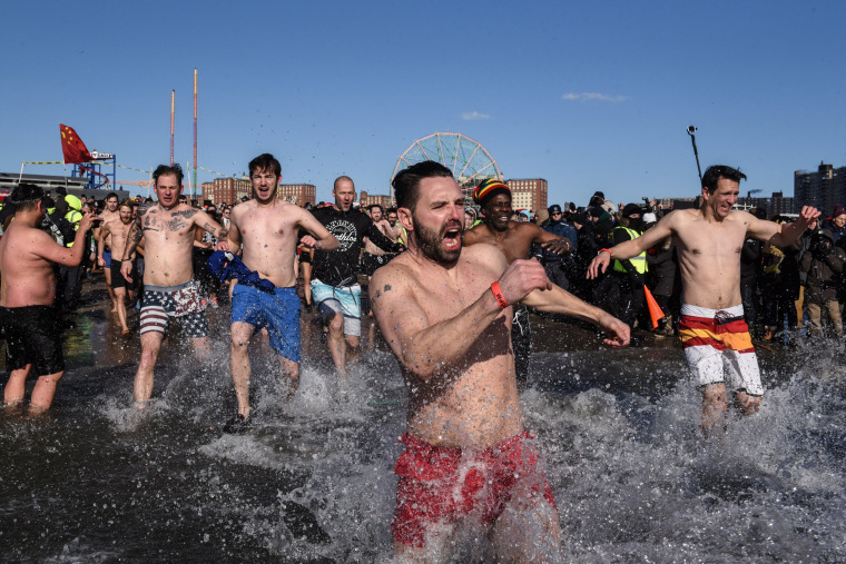 Image: Swimmers run into the water of the Atlantic Ocean during the Coney Island Polar Bear Club New Year's Day Plunge on Coney Island Beach in Brooklyn, New York City