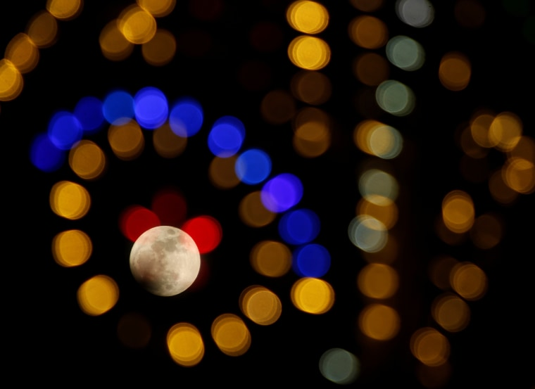 Image: The 'supermoon' full moon is seen through Christmas lights in Valletta