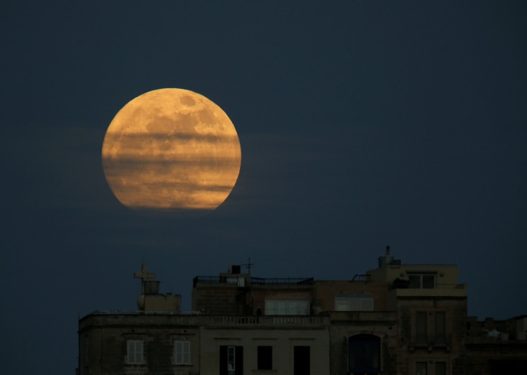 Image: A 'supermoon' full moon is seen rising in Pieta
