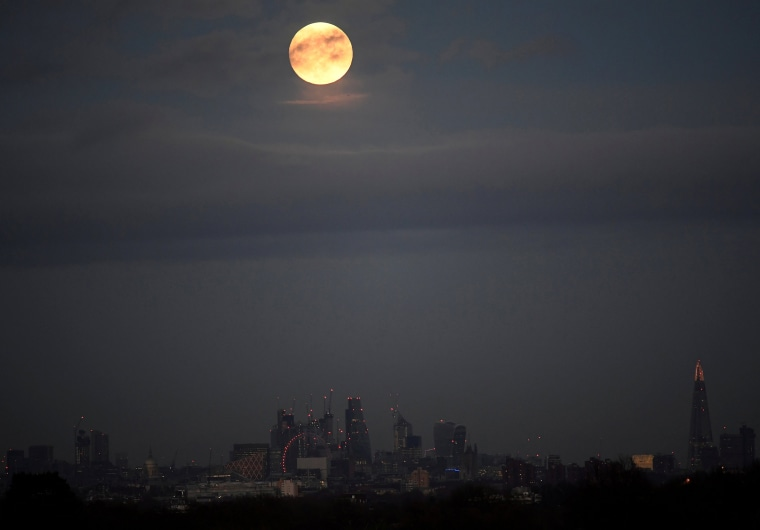 Image: A 'supermoon' full moon is seen rising above the skyline of London
