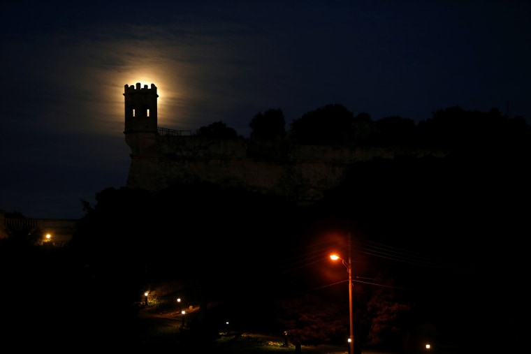 Image: A 'supermoon' full moon rises behind the guard tower on the 17th century San Salvatore Bastion in Pieta