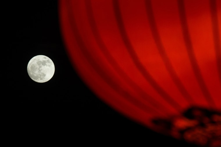 Image: The supermoon is seen rising behind a red lantern in Beijing