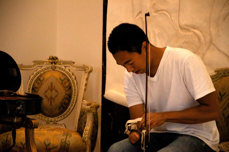 Adrian Anantawan adjusts the handle of his bow.