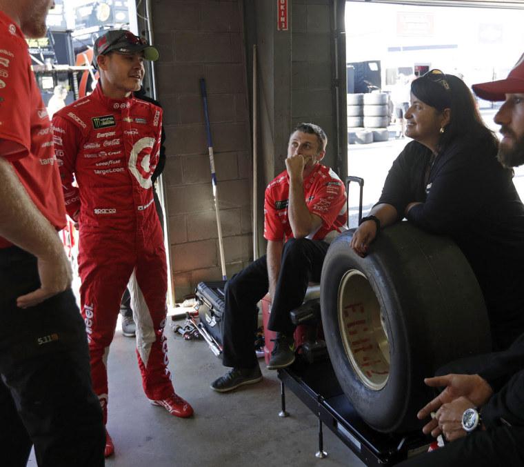 Alba Colon talks to a race car driver.