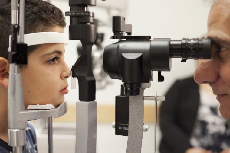 Image: A doctor checks the eyes of a patient who received a blindess gene therapy treatment