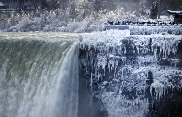 Image: Visitors take photographs at the brink of the Horseshoe Falls in Niagara Falls