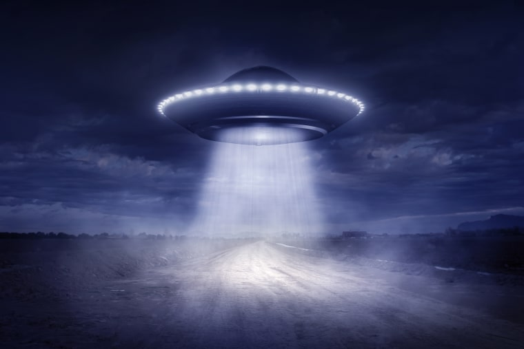 Alien spaceship landing on rural road