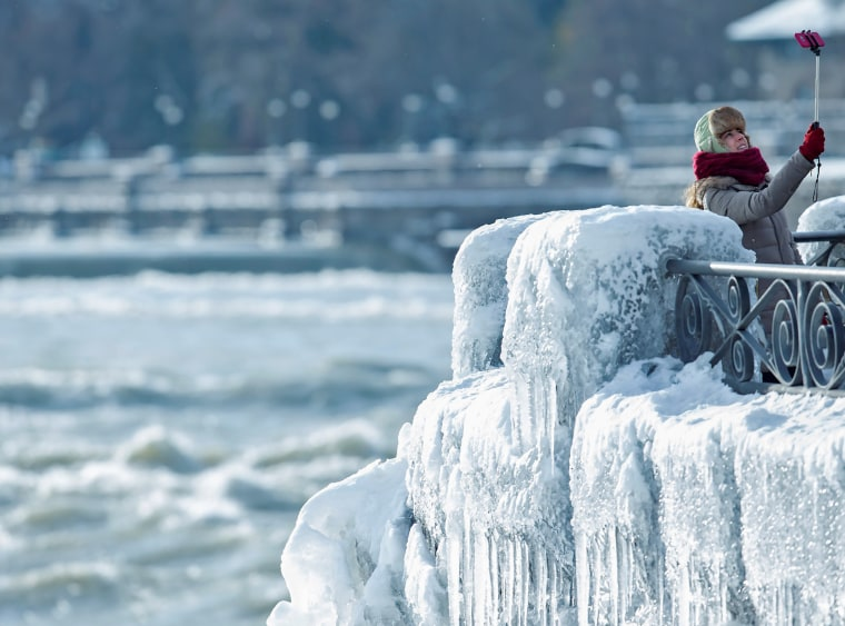 Image: A visitor takes pictures of ice covered Niagara Falls