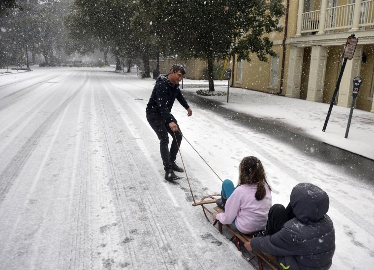 Image: Ramon Martinez takes advantage of little car traffic to pull a sleigh filled with his children Amy and Anthony down Bull Street toward Monterey Square, in Savannah