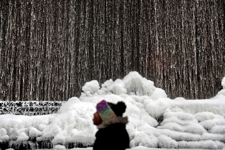 Image: Alora Freeman, 8, watches as ice builds along a downtown water fountain in Atlanta,