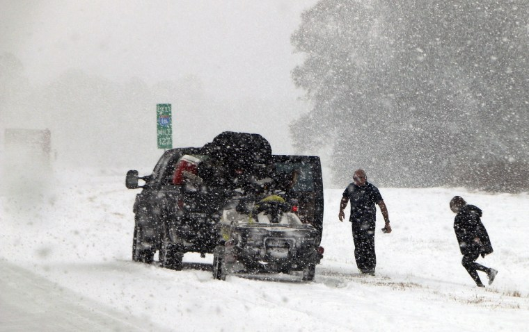 Image: People attend to their vehicle on Interstate 26, near Savannah