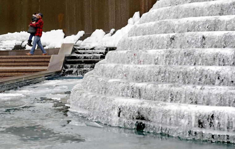 Image: Kenneth Freeman, carries his daughter Alora, 8, as they visit a frozen water fountain downtown in Atlanta,