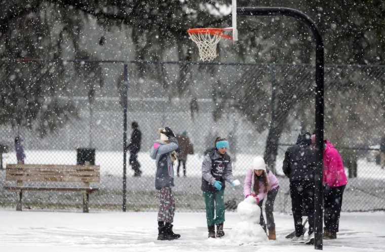 Image: Children from the Hoffman and Lynns families build a snowman on the public basketball courts in Forsyth Park