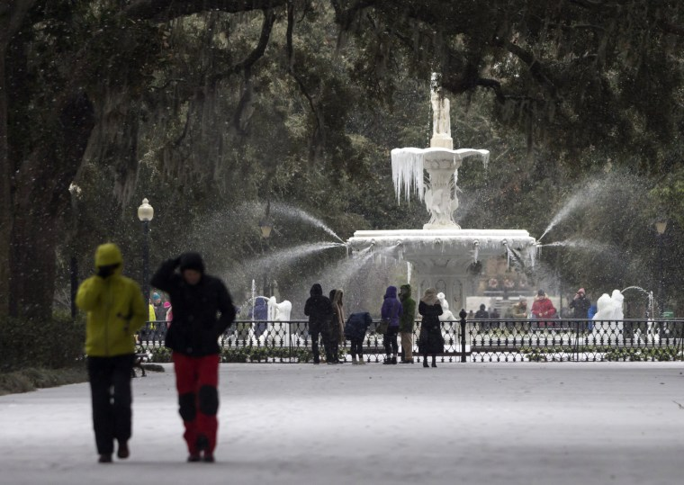 Image: Visitors walk around the frozen fountain and snow covered sidewalks at Forsyth Park