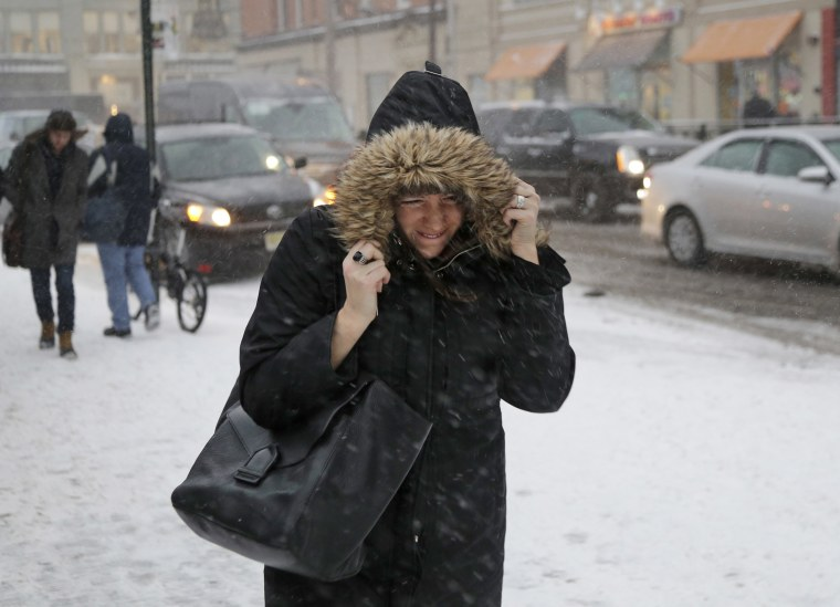 Image: A woman walks through the snow and wind in Hoboken