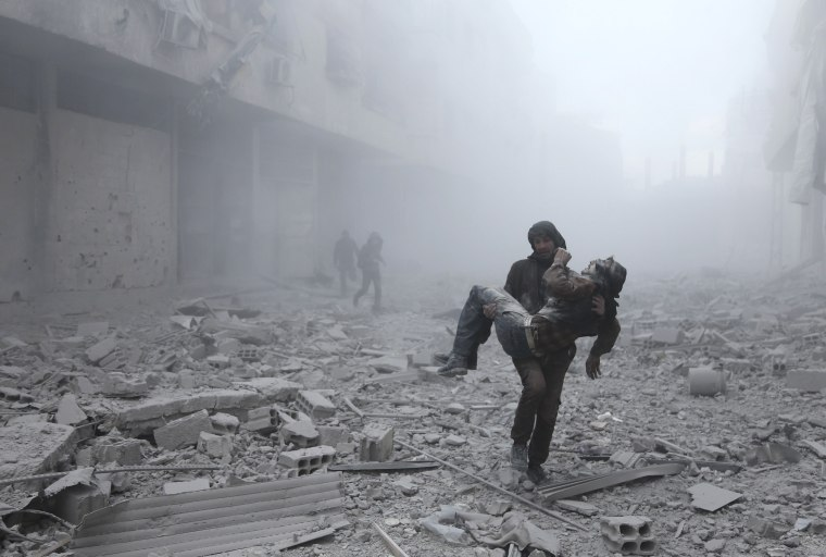 Image: A wounded man is carried following an air strike in Ghouta
