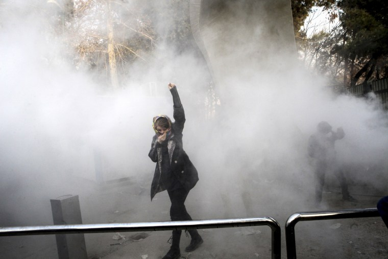 Image: A university student attends a protest inside Tehran University