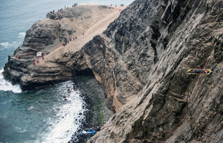 Image: Rescuers at the scene after a bus tumbled down a cliff