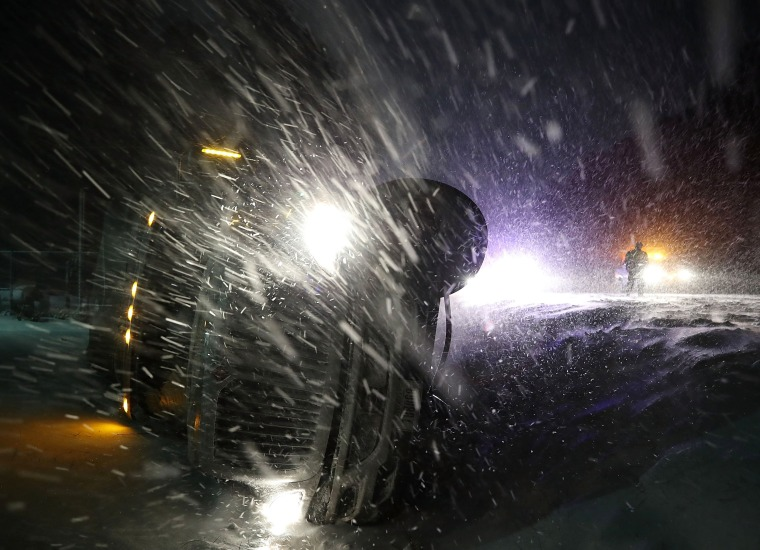Image: A tractor trailer lays on its side after running off the road during a snowstorm in Georgetown, Delaware