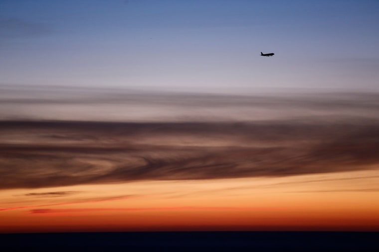 Image: A plane prepares to land at Barcelona airport during sunrise