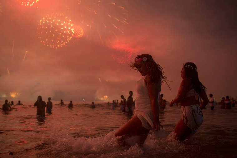 Image: People watch fireworks during New Years celebrations at Copacabana beach