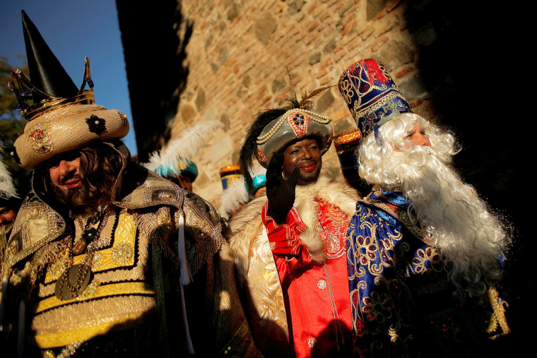 Image: Men dressed up as Gaspar, Balthasar and Melchior, the Three Wise Men, greet children during the traditional Epiphany parade in Malaga