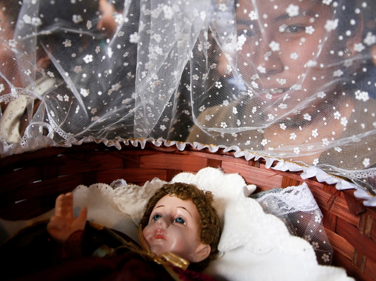 Image: A woman holds a statue of Jesus Christ during a traditional Catholic mass on Three Kings' Day in La Paz
