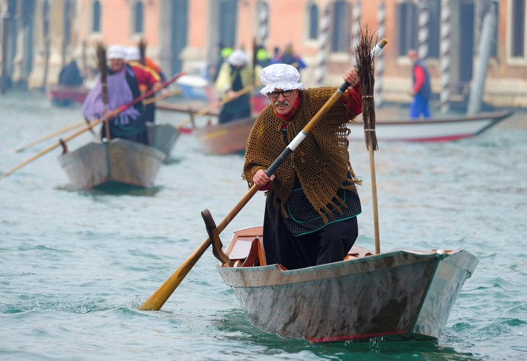 "Image: Men dressed as ""La Befana"", an imaginary old woman who is thought to bring gifts to children during the festival of Epiphany, row boats down the Grand Canal in Venice"