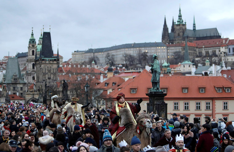 Image: Men dressed as the Three Kings greet spectators as they ride camels during the Three Kings procession across the medieval Charles Bridge in Prague