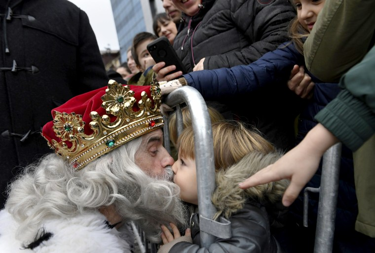 Image: A man dressed as one of the Three Wise Men kisses a child upon arriving at Poniente beach in Gijon