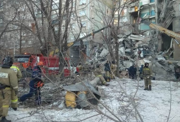 Image: Emergency personnel work at the site of collapsed apartment building after a suspected gas blast in Magnitogorsk