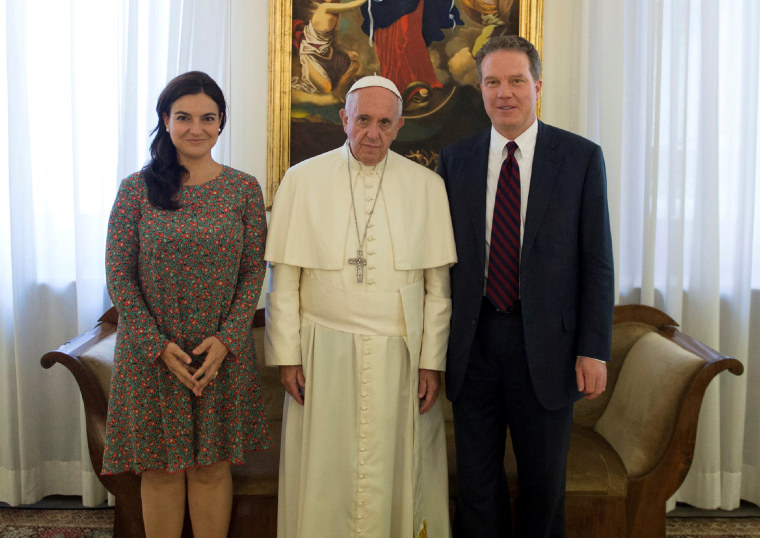 Image: FILE PHOTO: Pope Francis poses with Vatican spokesman Greg Burk and deputy Vatican spokesperson Paloma Garcia Ovejero during a meeting at the Vatican