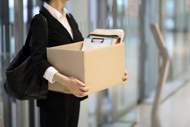 Businesswoman leaving office with box of personal items