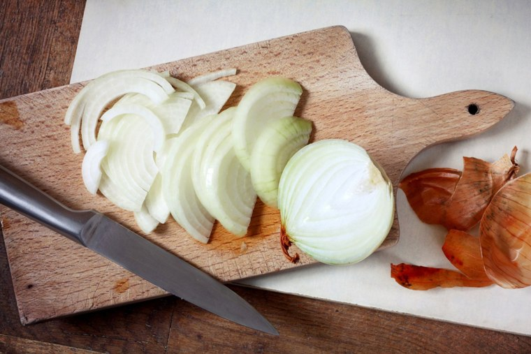 Sliced onion on wooden cutting board