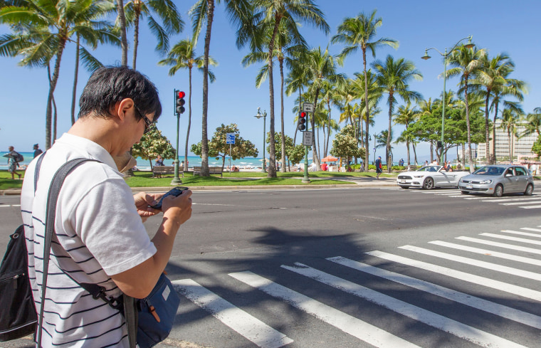 Image: A visitor texts before crossing the street in Waikiki on Oct,24, 2017 in Honolulu, Hawaii