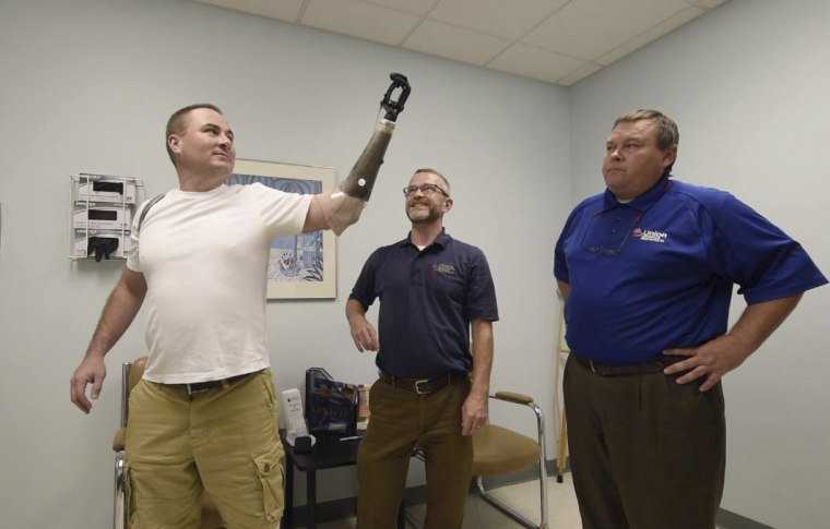 Leechburg Police Chief Michael Diebold, left, tries out his new prosthetic at Union Orthotics and Prosthetics in Lawrenceville, Pennsylvania, on Sept. 6.