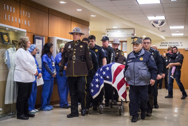 Image: Officers and medical staff take part in a procession for officer Daniel McCartney, of Yelm, at St. Joseph Medical Center in Tacoma, Washington, on Jan. 8, 2018.