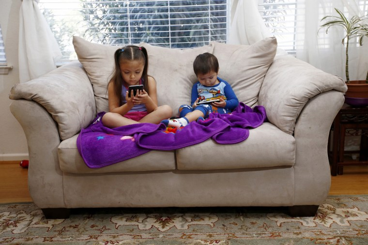 Image: Juliana Sanchez, 5, and her brother, Francisco Sanchez Jr., 2, watch children's programming on YouTube on their parent's cell phones at their home on March 9, 2015 in Mountain House, California.